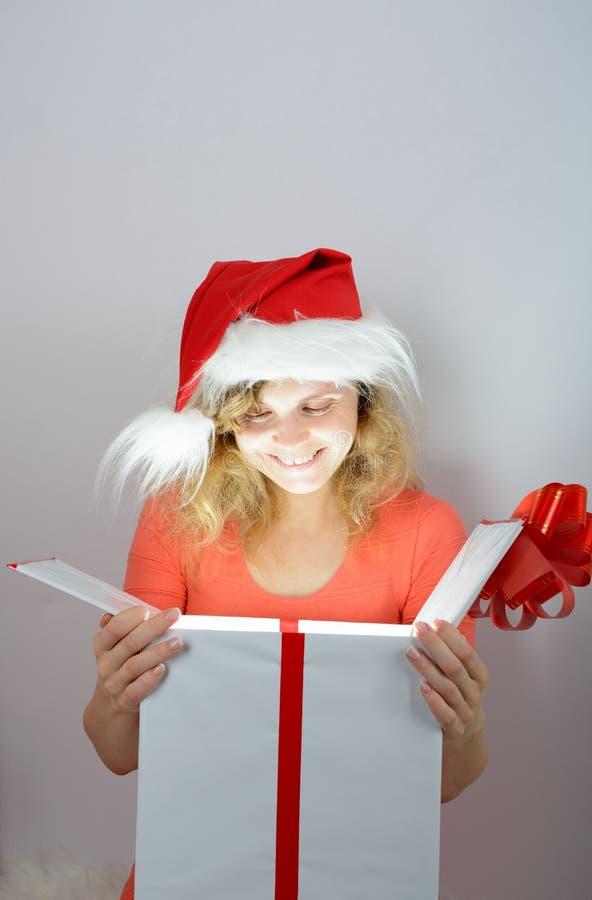 Muchacha en el sombrero de santa que abre una caja imagen de archivo libre de regalías