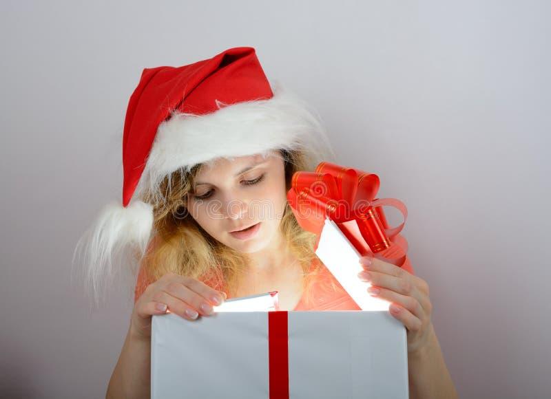 Muchacha en el sombrero de santa que abre una caja foto de archivo