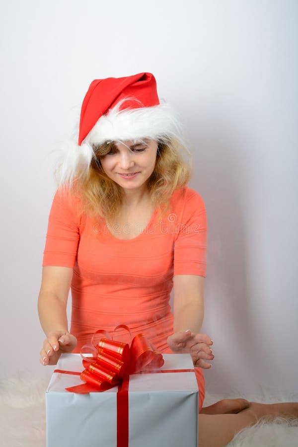 Muchacha en el sombrero de santa que abre una caja fotos de archivo libres de regalías