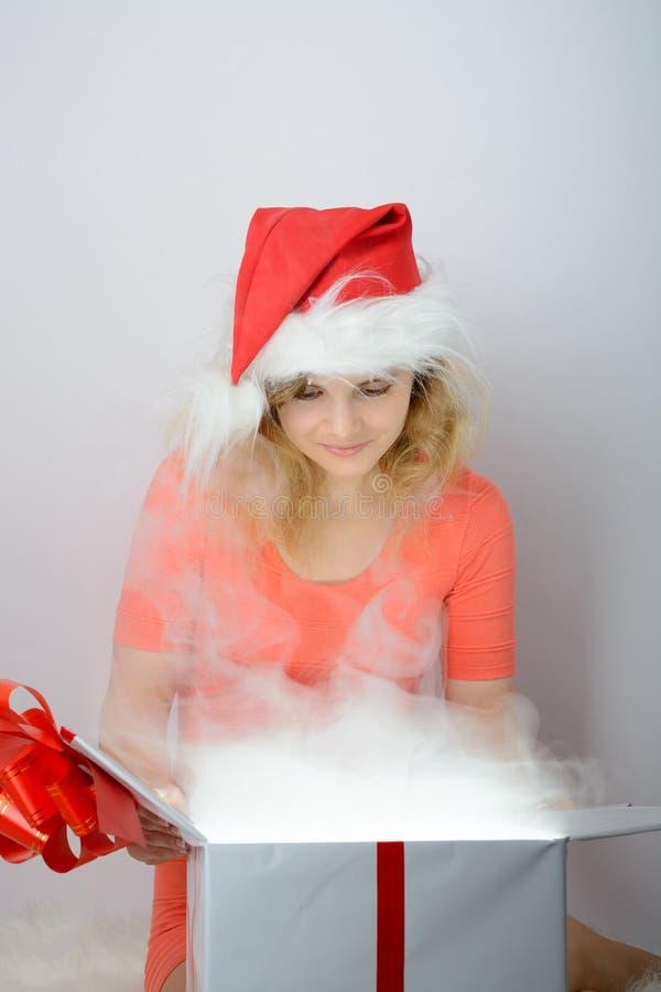 Muchacha en el sombrero de santa que abre una caja imagen de archivo