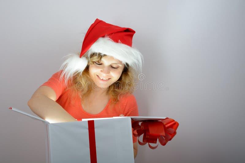 Muchacha en el sombrero de santa que abre una caja foto de archivo libre de regalías