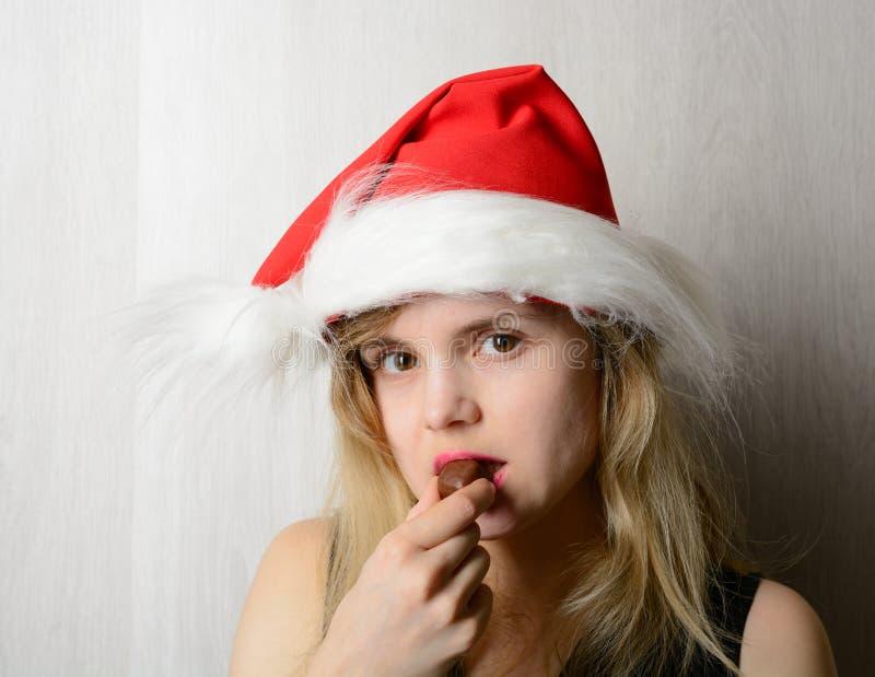Muchacha en el sombrero de santa que come el caramelo de chocolate foto de archivo