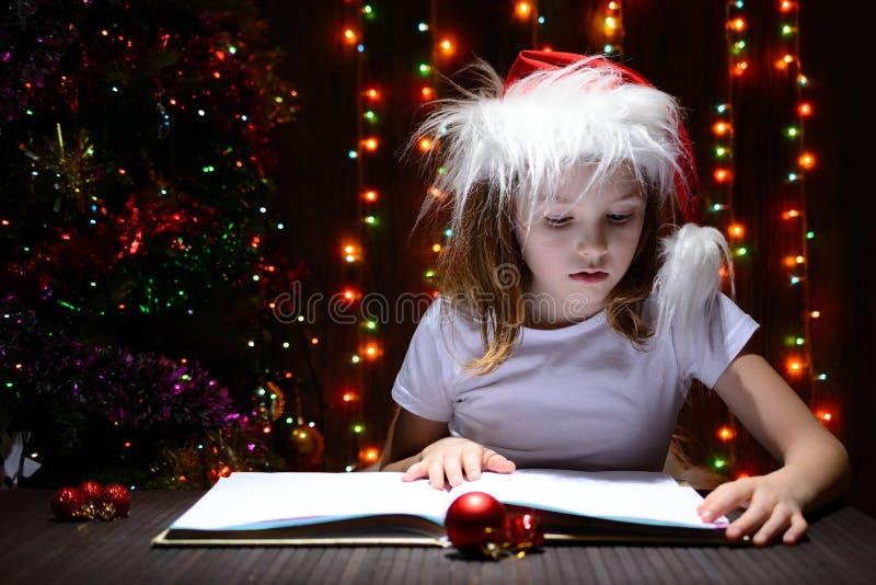 Muchacha en el sombrero de santa que lee un libro imagen de archivo