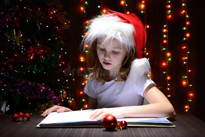 Muchacha en el sombrero de santa que lee un libro imagenes de archivo