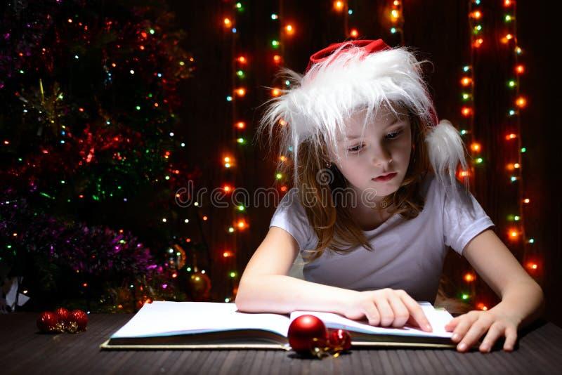 Muchacha en el sombrero de santa que lee un libro fotos de archivo libres de regalías