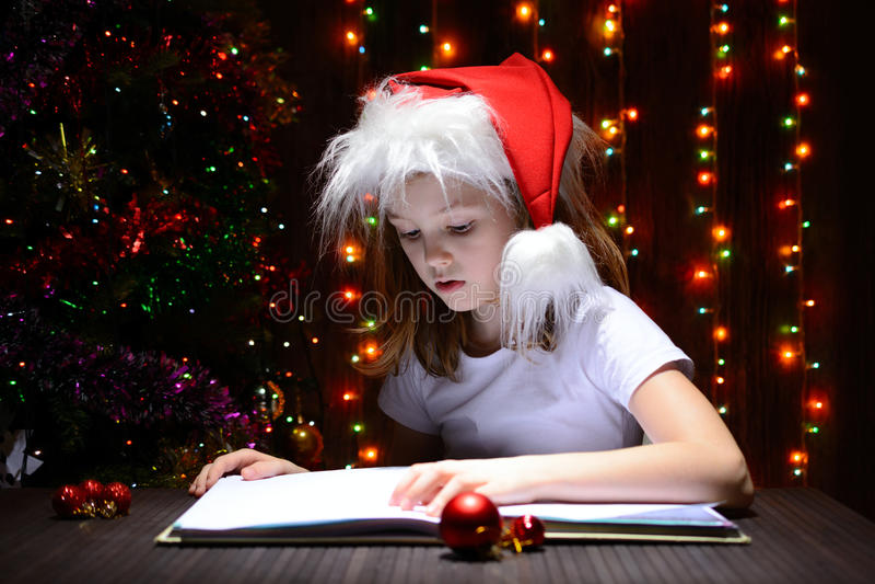 Muchacha en el sombrero de santa que lee un libro fotografía de archivo libre de regalías