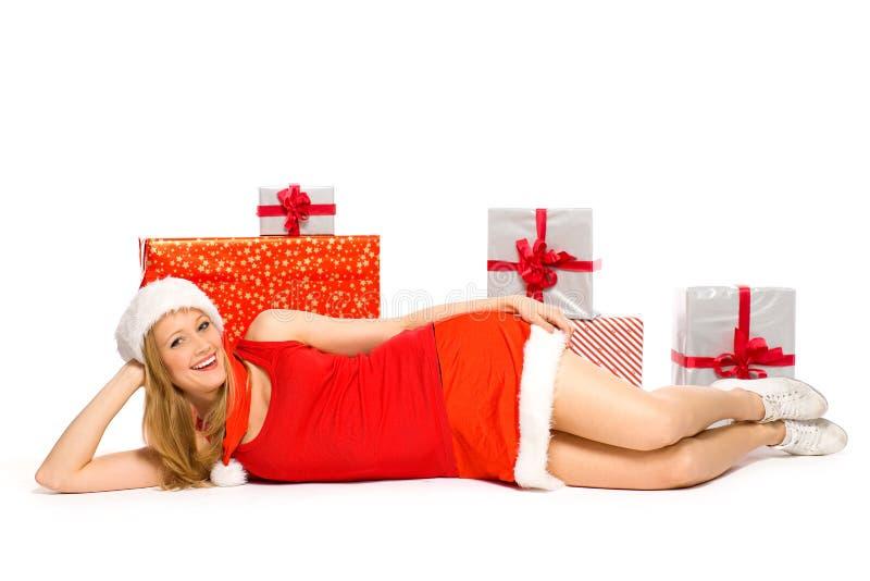 Muchacha en el sombrero de Santa que se acuesta con los regalos imágenes de archivo libres de regalías