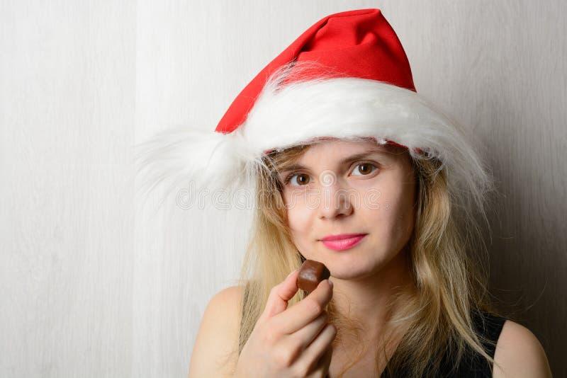 Muchacha en el sombrero de santa que sostiene el caramelo imágenes de archivo libres de regalías