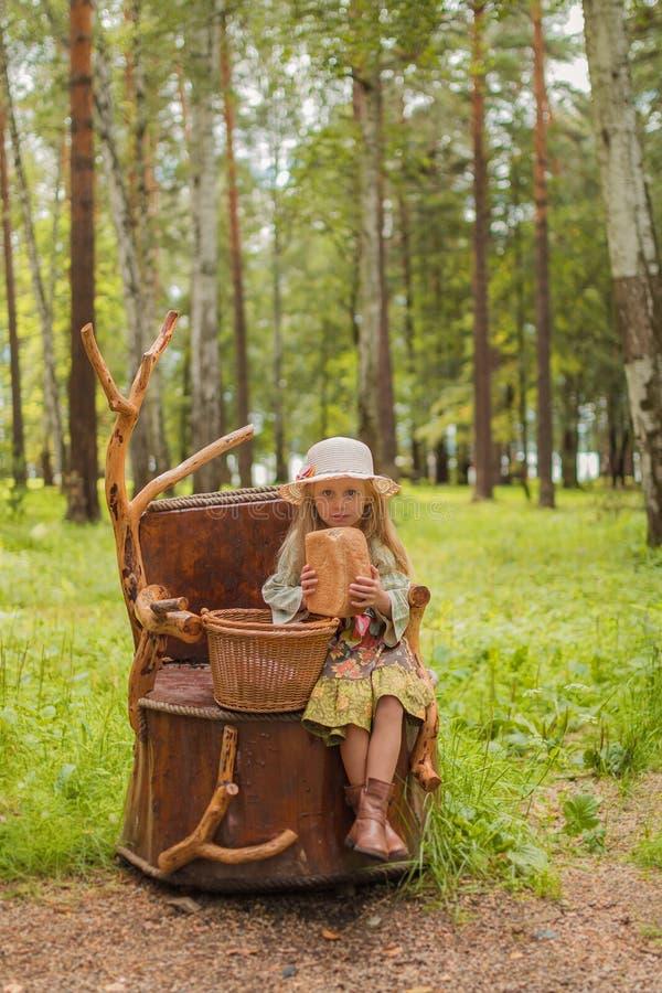 Muchacha en el sombrero y el vestido rústicos y botas que se sientan en un tocón de árbol en el bosque con una cesta de pan y de  imagenes de archivo
