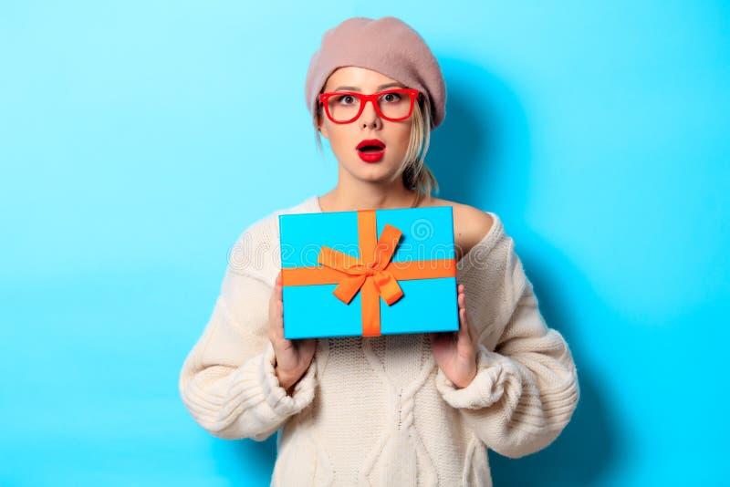 Muchacha en el suéter blanco con la caja de regalo imagen de archivo