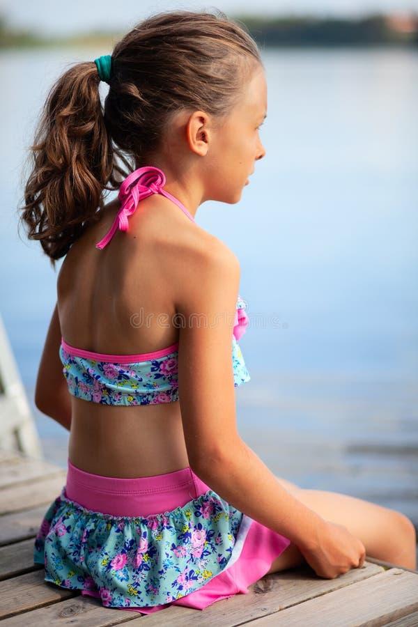 Muchacha en el traje de baño que se sienta en el lago Relajaci?n en el embarcadero Adultos jovenes imágenes de archivo libres de regalías