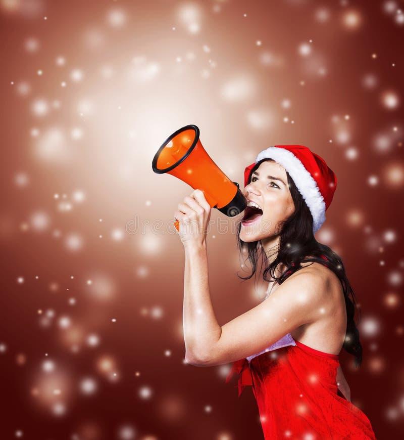 Muchacha en el traje de Santa Claus con un megáfono en fotografía de archivo libre de regalías