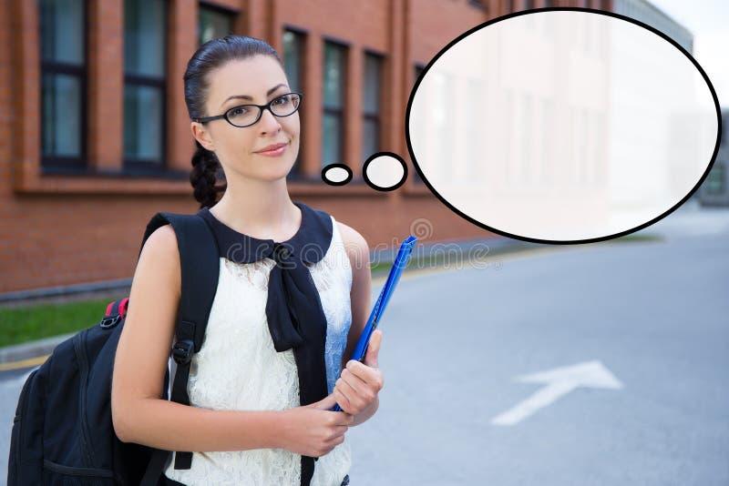 Muchacha en el uniforme escolar que se coloca en campus y que piensa en som fotografía de archivo libre de regalías