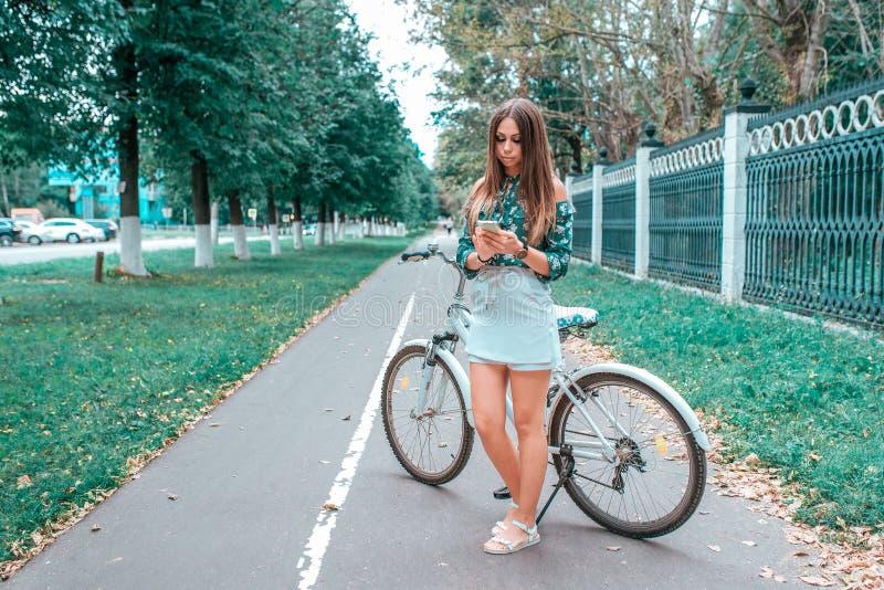 Muchacha en el verano en la ciudad, colocándose al lado de la bici, sosteniendo un smartphone en sus manos, escribiendo un mensaj fotos de archivo libres de regalías