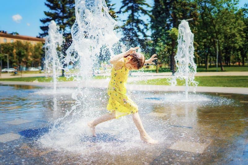 Muchacha en el vestido amarillo que juega y que se divierte que disfruta del espray de la fuente imágenes de archivo libres de regalías