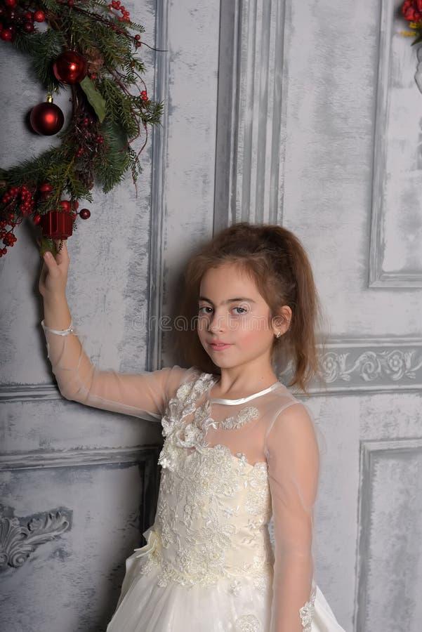 Muchacha en el vestido blanco al lado de la guirnalda de la Navidad imágenes de archivo libres de regalías