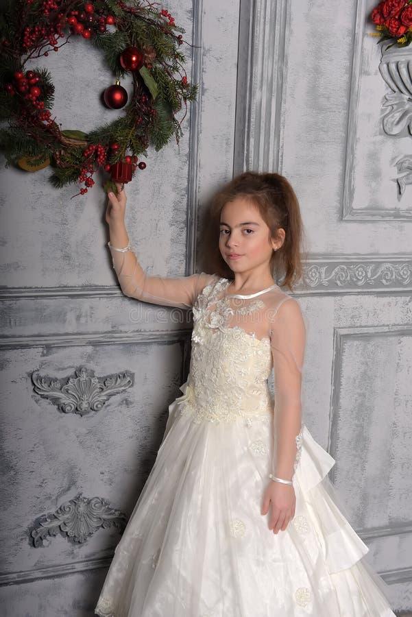 Muchacha en el vestido blanco al lado de la guirnalda de la Navidad fotos de archivo libres de regalías