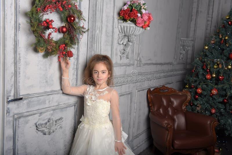 Muchacha en el vestido blanco al lado de la guirnalda de la Navidad fotografía de archivo libre de regalías
