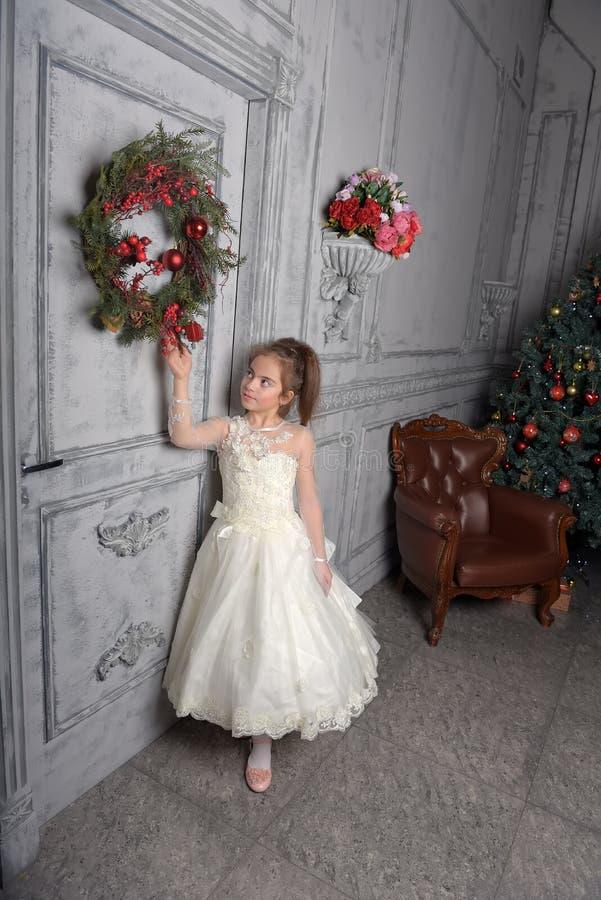 Muchacha en el vestido blanco al lado de la guirnalda de la Navidad fotos de archivo