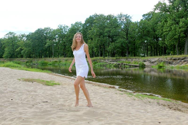 Muchacha en el vestido blanco del cordón en la playa imagenes de archivo
