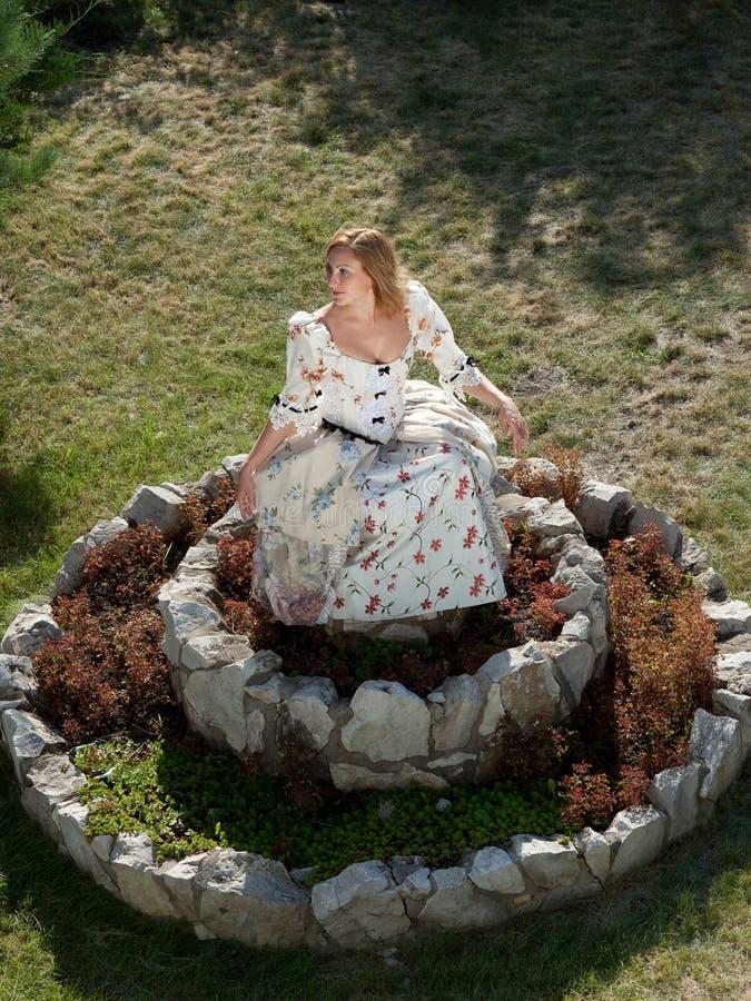 Muchacha en el vestido blanco que se coloca en el macizo de flores de piedra imagen de archivo libre de regalías