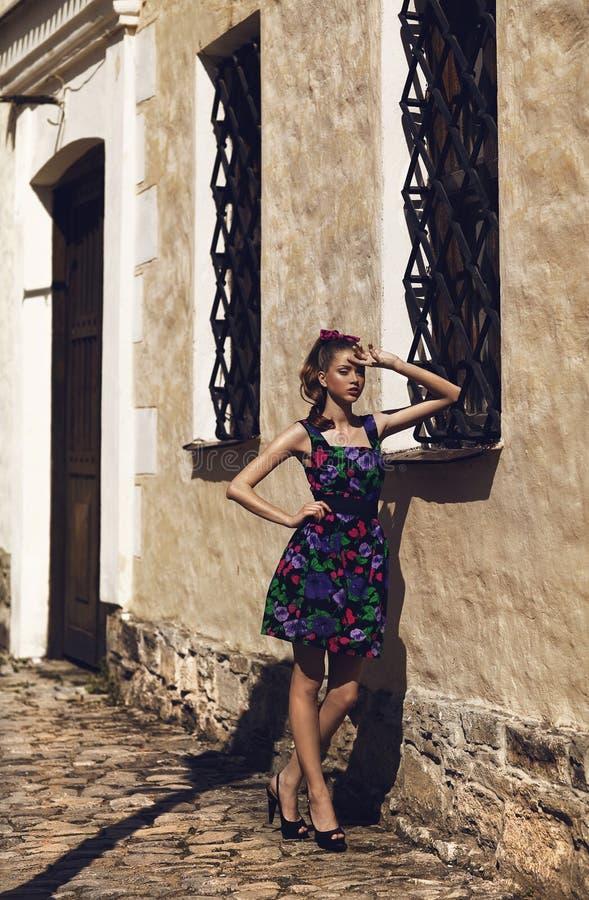 Muchacha en el vestido de flores que presenta afuera imagen de archivo libre de regalías