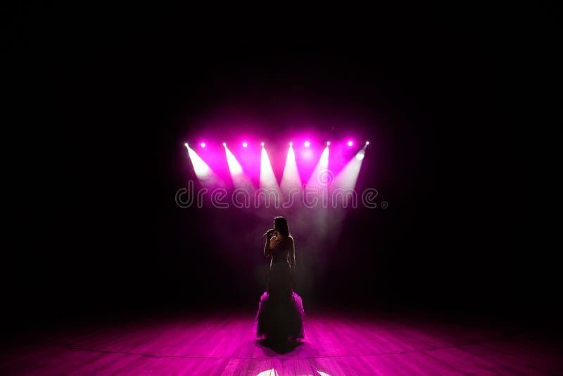 Muchacha en el vestido largo que se realiza en etapa Muchacha que canta en la etapa delante de las luces Silueta de la situación  imagen de archivo libre de regalías