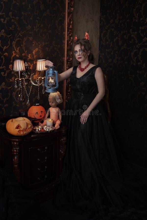 Muchacha en el vestido negro de Halloween en traje del diablo con los cuernos rojos imágenes de archivo libres de regalías