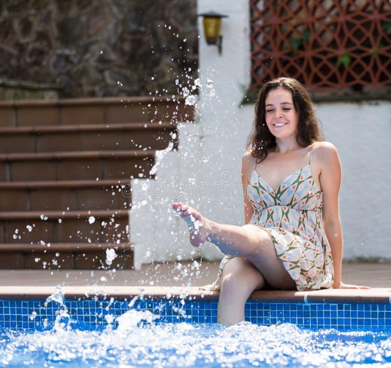 Muchacha en el vestido que descansa cerca de piscina fotos de archivo libres de regalías