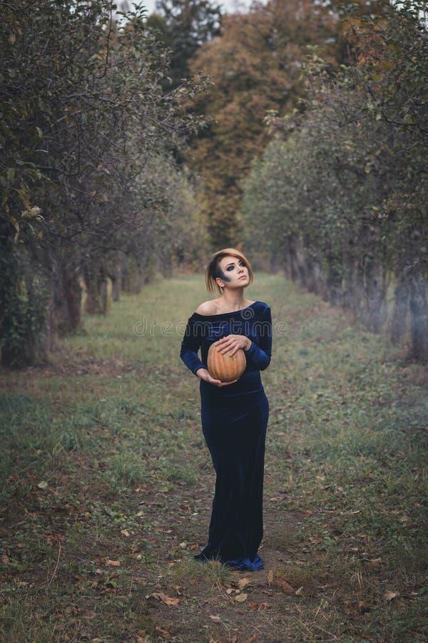 Muchacha en el vestido que sostiene una calabaza foto de archivo libre de regalías