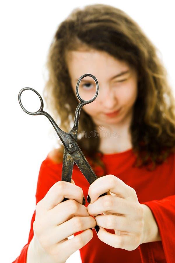 Muchacha en el vestido rojo que se ríe con las tijeras del vintage - mirando foto de archivo