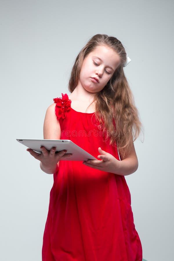 Muchacha en el vestido rojo que sostiene la tableta digital fotografía de archivo