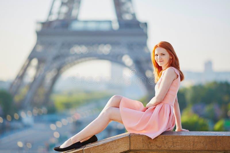 Muchacha en el vestido rosado cerca de la torre Eiffel, París imagenes de archivo