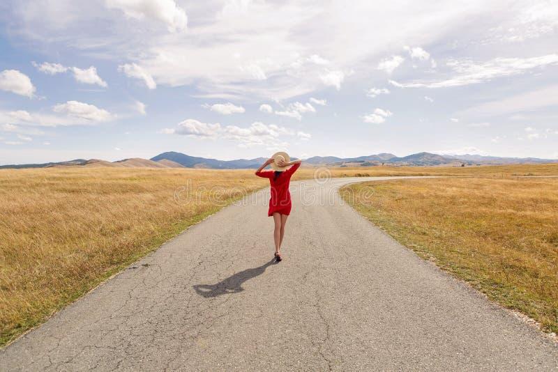 Muchacha en el vestido y el sombrero rojos que camina a lo largo del camino en las montañas imagen de archivo libre de regalías