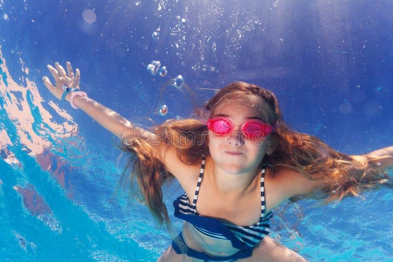 Muchacha en gafas que aprende conteniendo la respiración subacuática imagen de archivo