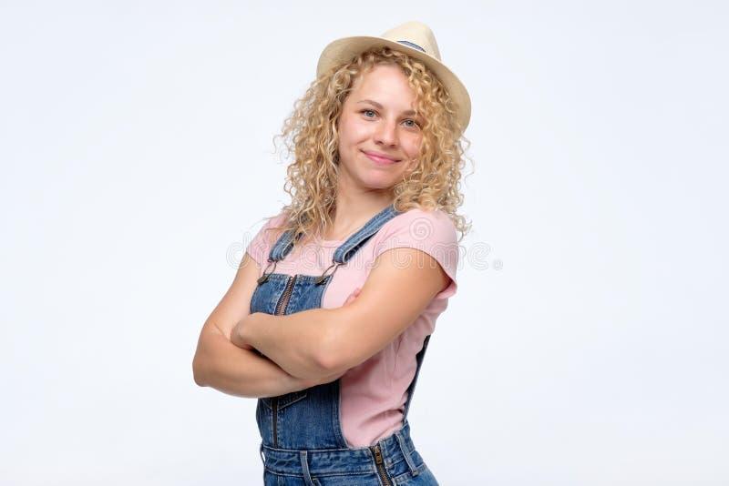 Muchacha en guardapolvos del dril de algodón y sombrero del verano con la sonrisa doblada de las manos foto de archivo