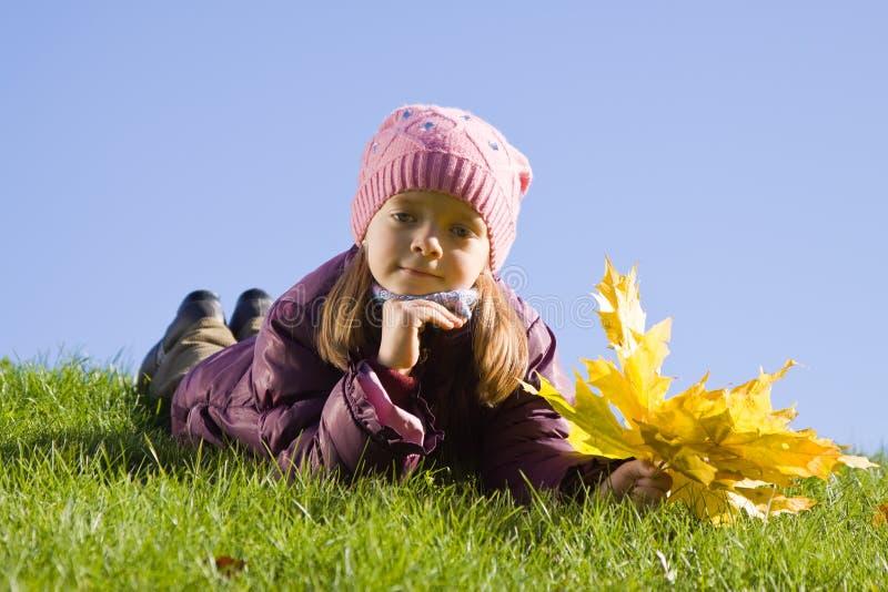 Muchacha en hierba contra el cielo fotografía de archivo