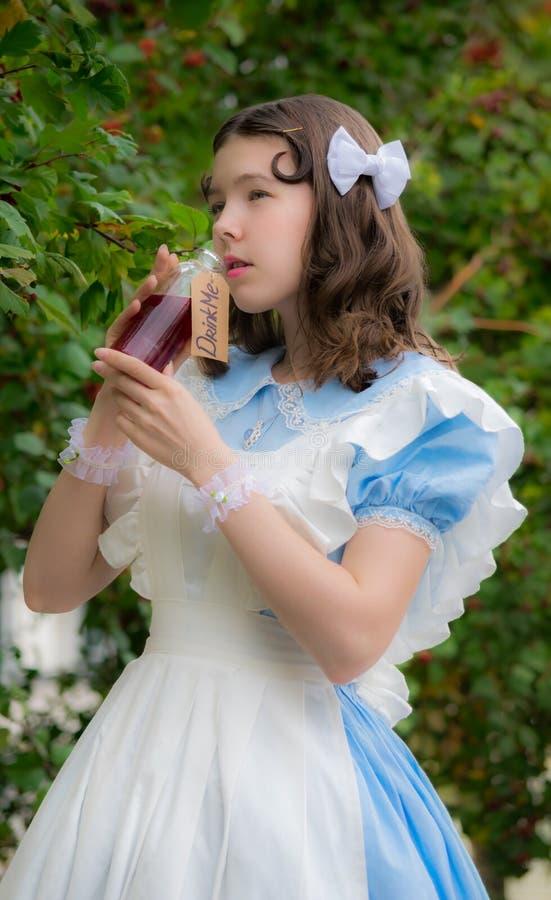 Muchacha en imagen de la bebida de las bebidas de la heroína del cuento de hadas de la botella de cristal imágenes de archivo libres de regalías