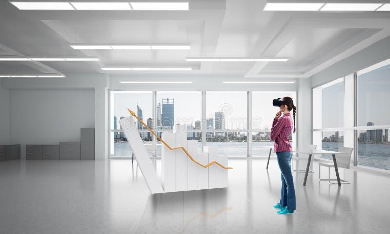 Muchacha en interior de la oficina en máscara de la realidad virtual usando tecnologías innovadoras Técnicas mixtas foto de archivo