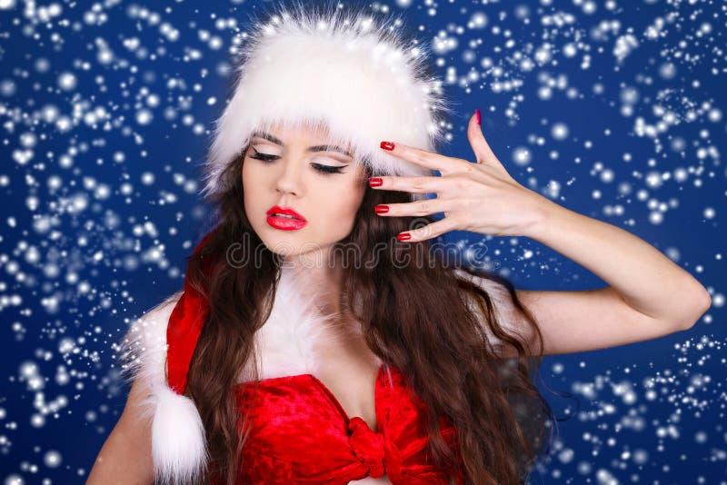 Muchacha en la alineada roja de Papá Noel que presenta en nieve imagenes de archivo