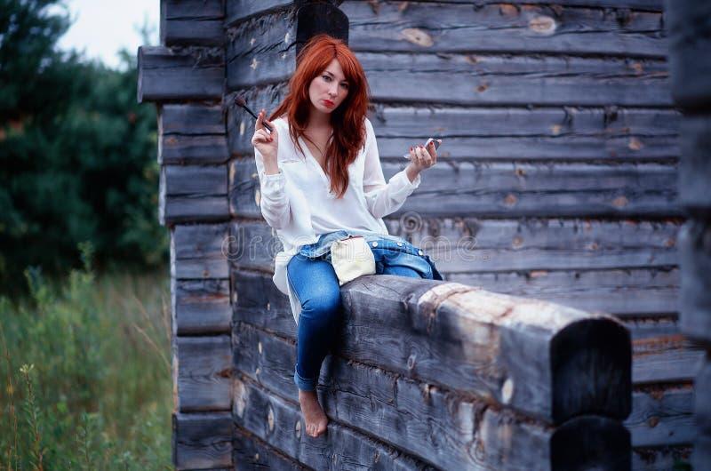Muchacha en la camisa blanca y los tejanos que hacen maquillaje fotografía de archivo