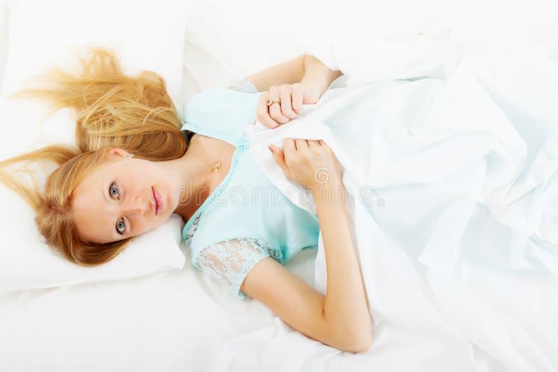 Muchacha en la camisa de dormir que miente en la hoja blanca en cama en casa imagenes de archivo