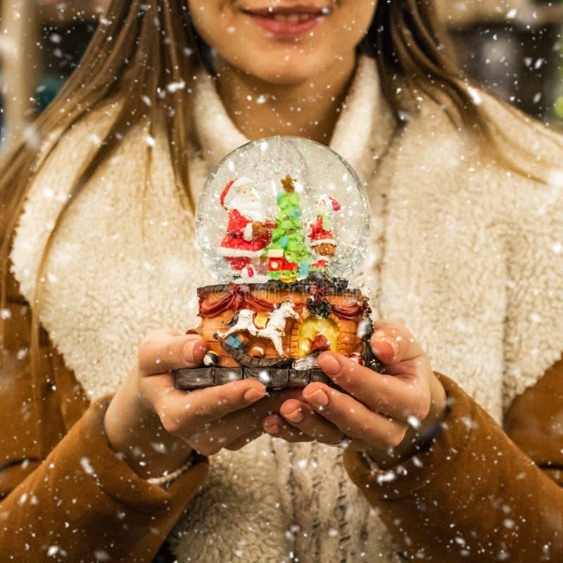 Muchacha en la capa caliente que sostiene la bola de cristal con los abetos, la casa y la nieve artificial en una alameda en la f fotografía de archivo