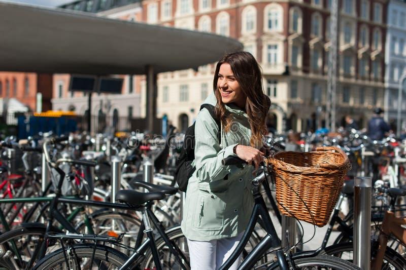 Muchacha en la ciudad con la bici con un espacio de estacionamiento para el backgroung de las bicicletas imagen de archivo libre de regalías