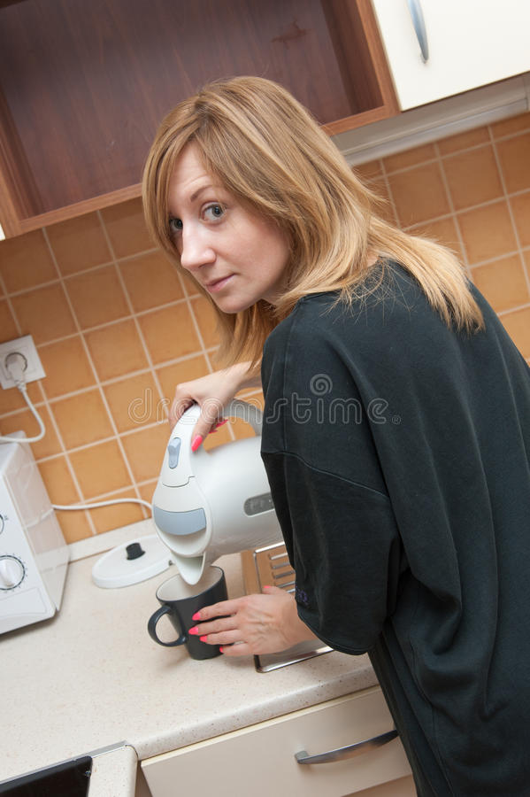 Muchacha en la cocina que hace té fotografía de archivo libre de regalías