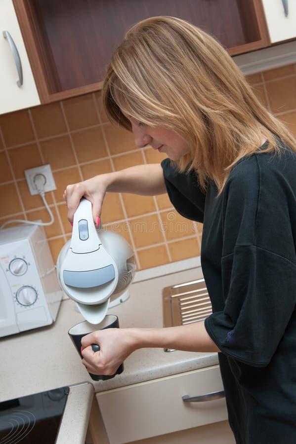 Muchacha en la cocina que hace té fotos de archivo