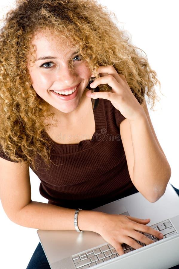 Muchacha en la computadora portátil y el teléfono