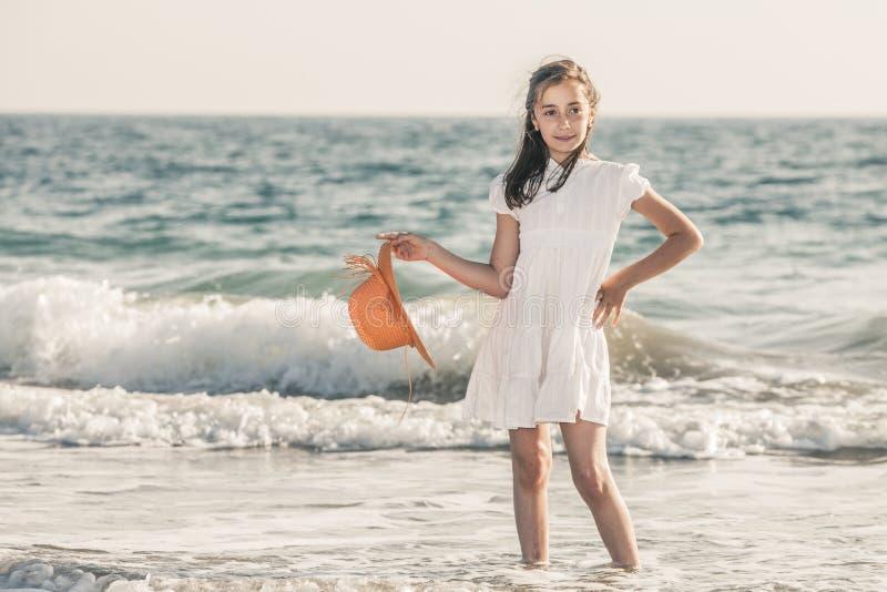 Muchacha en la costa que lleva un sombrero anaranjado y un vestido blanco imagenes de archivo