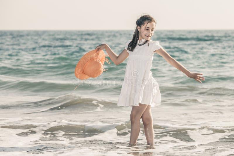 Muchacha en la costa que lleva un sombrero anaranjado y un vestido blanco imagen de archivo