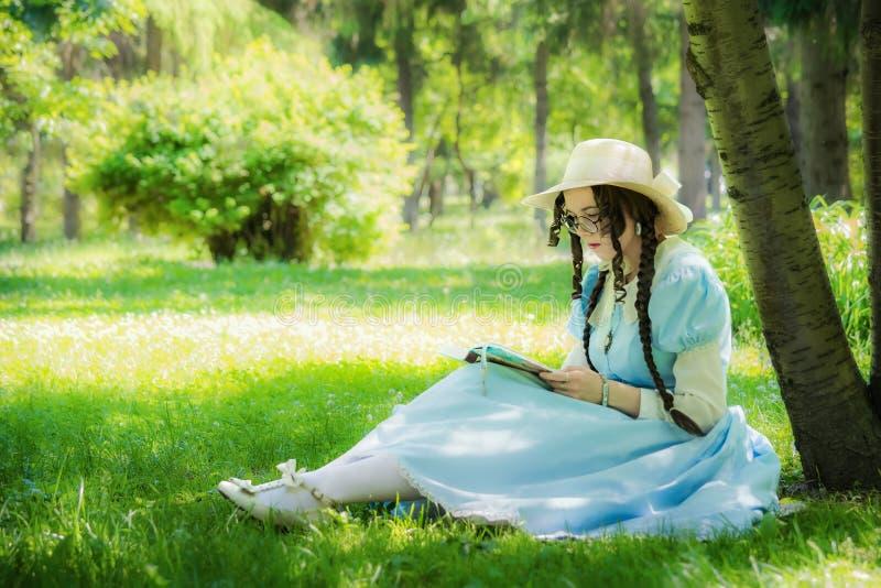 Muchacha en la imagen de la heroína de una hada que se sienta debajo de un árbol fotos de archivo libres de regalías